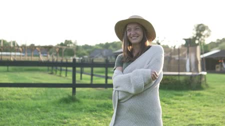 dusk : Beautiful woman in a hat walks at sunset on an eco-farm. Slow shooting