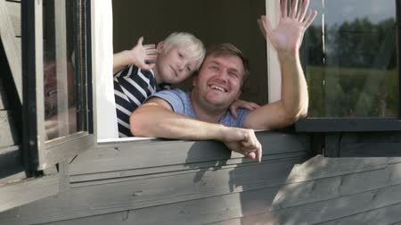 okno : Dad and son slowly wave their hands out the window. A man with a blond boy say goodbye to the guests from the window of a wooden house on a farm in the summer