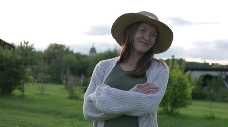 namiot : Stylish woman farmer in a hat walks in the summer at sunset on the field
