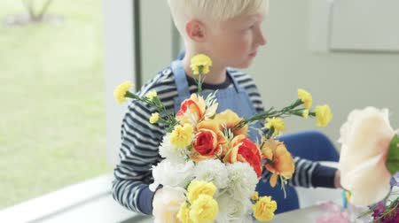 pioenroos : A boy collects a bouquet of artificial flowers in the childrens city of professions Kidsburg Stockvideo