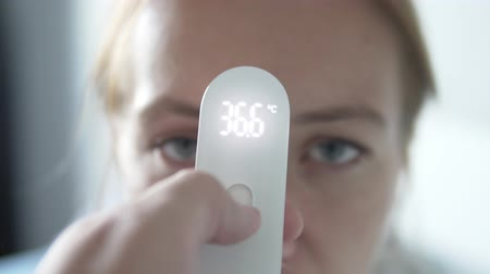 čelo : checking a woman is temperature with an electronic thermometer. Thermometer in focus, face blurry in the background. Ideal temperature Dostupné videozáznamy
