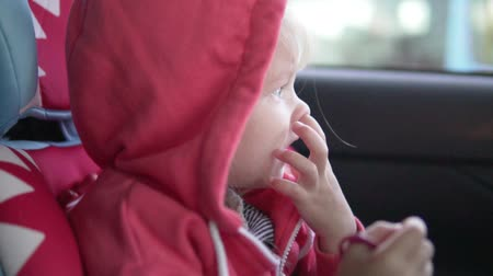 carseat : Girl crying in a car seat. Sad little girl rides in a car in the car seat