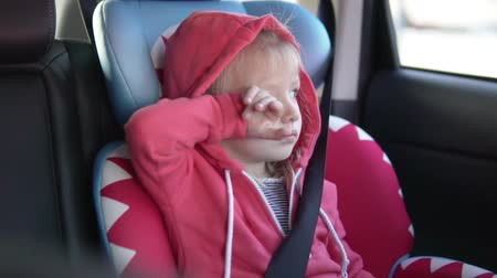carseat : Girl rides in a car in a car seat. A child falls asleep in a car seat in a car Stock Footage