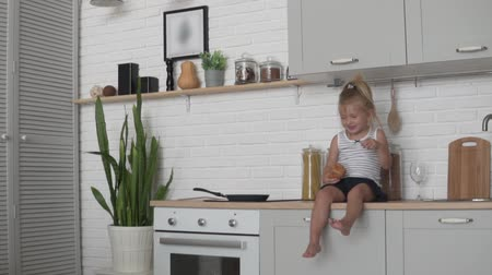 nevetséges : Funny little girl sitting in the kitchen and eagerly eating a loaf of white bread. A child sits in the kitchen with a baguette of bread