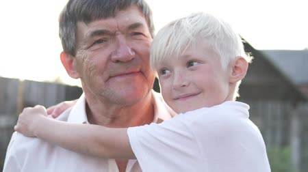 holidays : Boy hugs grandfather at sunset. Happy grandfather with grandson. Slow Motion Close-up