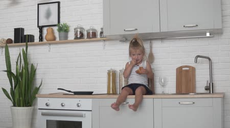 nevetséges : Little girl eating bread in the kitchen.