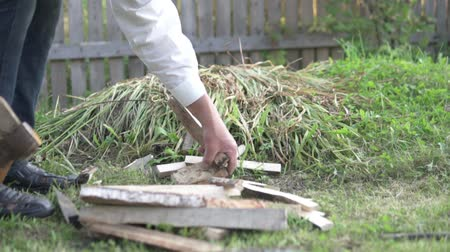 топор : A man stabs firewood in the garden with an ax. Стоковые видеозаписи