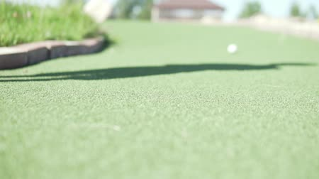 golfové hřiště : Throw the ball in golf. White ball rolls into a hole on a green field