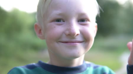 szeplők : Closeup of a blond boy. The child covers his face with his hands, then opens and smiles. Slow motion