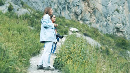hayran olmak : A woman in the mountains looks at a beautiful landscape. girlfriends on a mountain hike in Altai