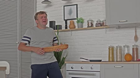pronto a comer : A man having fun with a loaf of white bread. Dude plays the gleb as he sings and laughs on the guitar Stock Footage