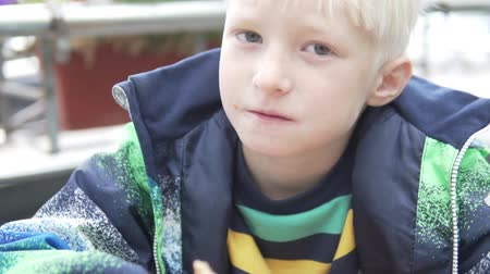 houska : Handsome blond boy eagerly eats a cheeseburger on the street in autumn. Close-up of a boy with a hamburger