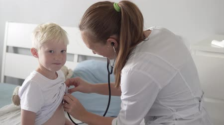 hemşire : The doctor listens with a stethoscope to a boy in a clinic. Doctor listens to a teenager with a stethoscope