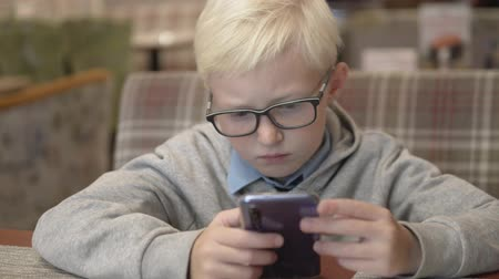mobilitás : A serious boy with glasses sits in a cafe and plays on a mobile phone. A child with glasses carefully looks at the screen of a mobile phone in a cafe Stock mozgókép