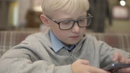caffe : A boy with glasses plays chess on a mobile phone. Serious child plays a game on the phone