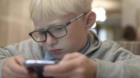 caffe : The boy with glasses carefully looks at the screen of a mobile phone at a table in a cafe.