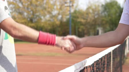tennis whites : Handshake of two tennis players after playing on a clay court against the background of the net