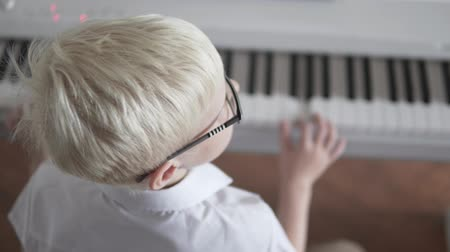 Albino boy in a white shirt plays the piano. The view from the back. A child tunes an electronic piano Dostupné videozáznamy