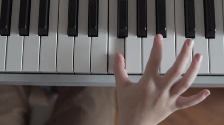 Childrens hand plays the piano. Small hand presses the keys of a piano, close-up