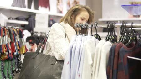 Beautiful young woman chooses a shirt for her child in a shopping center. A woman takes off a hanger with a shirt and looks at her carefully Stock Footage