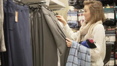 Beautiful woman chooses mens pajamas in a store. Shopper watches mens home pants.