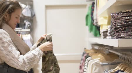 A customer in a childrens clothing store. Woman is studying the composition of the pants by the tag on the clothes Stock Footage