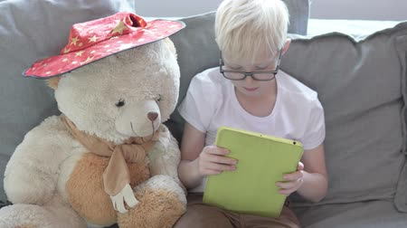 Cute blond boy plays games on the tablet. Next to the child sits a large teddy bear in a wizards hat Stock Footage