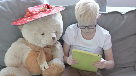 A blond boy is watching cartoons on a tablet at home on the couch. A child sits next to a big teddy bear and plays a game on a tablet
