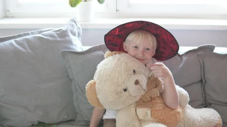 Cute boy hugs beloved teddy bear. Boy in a magic hat gently hugs a plush toy and smiles