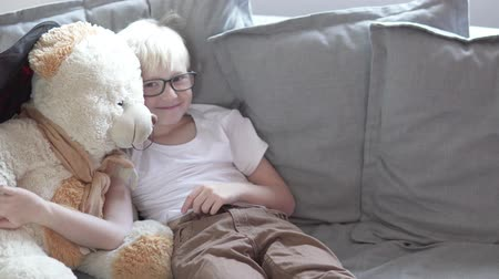 Beautiful boy schoolboy plays at home with a teddy bear.