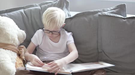 A blond boy is looking at his children is photo album. A child flips through pages of a book with photos and smiles.