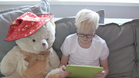A blond boy plays games on a tablet. A child with a tablet and a big teddy bear is sitting on the sofa at home. Stock Footage