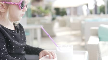 Stylish little blonde girl drinks a milkshake in a summer cafe. A child in pink sunglasses drinks a cocktail from a straw in a cafe. Close-up