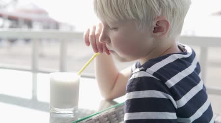 Cute blond boy drinks a milkshake in a cafe on a hot summer day.