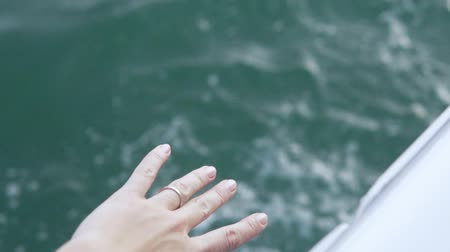 female hand reaches for the sea from a yacht. Female hand touches water from a yacht Dostupné videozáznamy