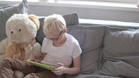 Cute blond boy playing tablet at home on the couch.
