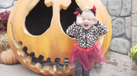 Little funny girl celebrates halloween. A baby in a suit stands by a giant pumpkin and laughs Stock Footage