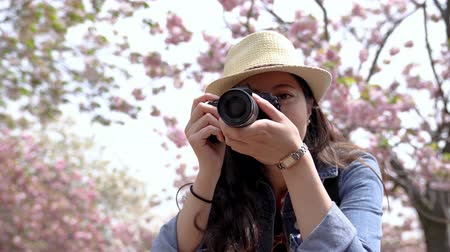 osaka : a beautiful woman turning around cheerfully and taking a photo at camera in the park Stock Footage