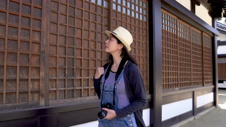 osaka : a beautiful travel woman walking and looking at the wooden grid windows in a  famous temple of osaka in japan.