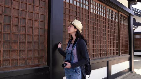 osaka : a beautiful travel woman looking and touching the wooden grid windows in a  famous temple of osaka in japan.