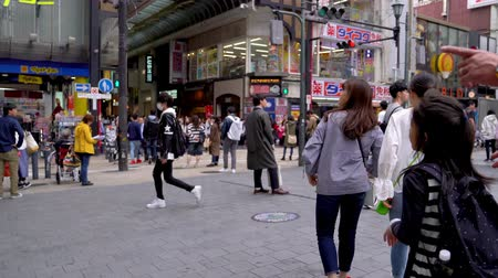 osaka : Osaka, Japan-April 14, 2018: people walking on the road in the famous shopping area in Japan Stock Footage