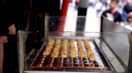 kalmar : Osaka, Japan-April 14, 2018: hungry client orders Japanese traditional street food in the takoyaki vendor