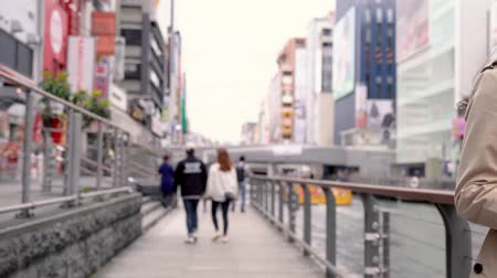 handrails : Osaka, Japan-April 14, 2018: Japanese young couple dating and relaxing walking along the river Stock Footage