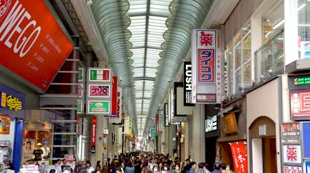 hirdet : Osaka, Japan-April 14, 2018: crowd slowly walking and shopping in the most famous shopping area in Osaka, Japan Stock mozgókép