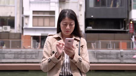 osaka : Osaka, Japan-April 14, 2018: Japanese office lady relying on the handrail, next to the river, using cellphone to text the messages Stock Footage