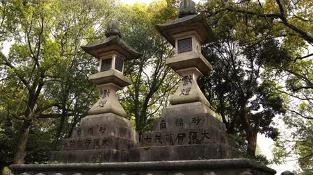 lanterns : NARA, JAPAN - APRIL 16, 2018: Stone lamps which prayers respectfully offer to the temple peacefully standing in the forest Stock Footage