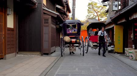 lehúzó : Kyoto, JAPAN - APRIL 18, 2018: pulled rickshaw driver working hard and introducing the Japanese temple to the passengers