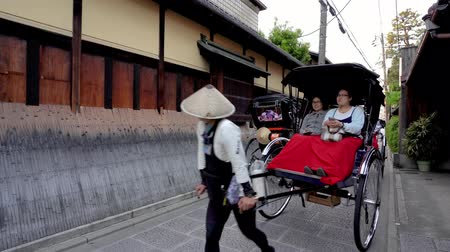 risciò : Kyoto, JAPAN - APRIL 18, 2018: rickshaw puller helping his passengers taking photo on the car on the street by cellphone