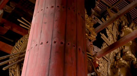 gigante : huge golden god statue sitting in the red wooden temple.Translation of the sign  Empty God with no desire.