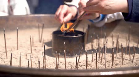 nimet : people burning incense sticks in the burner for praying the god in the temple Stok Video